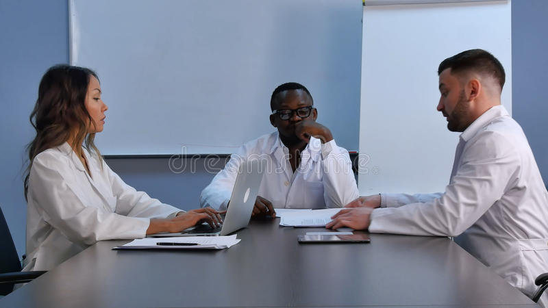 Equipo médico sonriente usando el ordenador portátil a trabajar, discutiendo la nueva medicina fotos de archivo