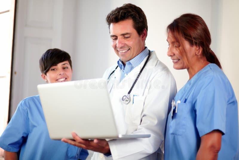 Equipo médico usando un ordenador portátil mientras que se coloca fotografía de archivo libre de regalías