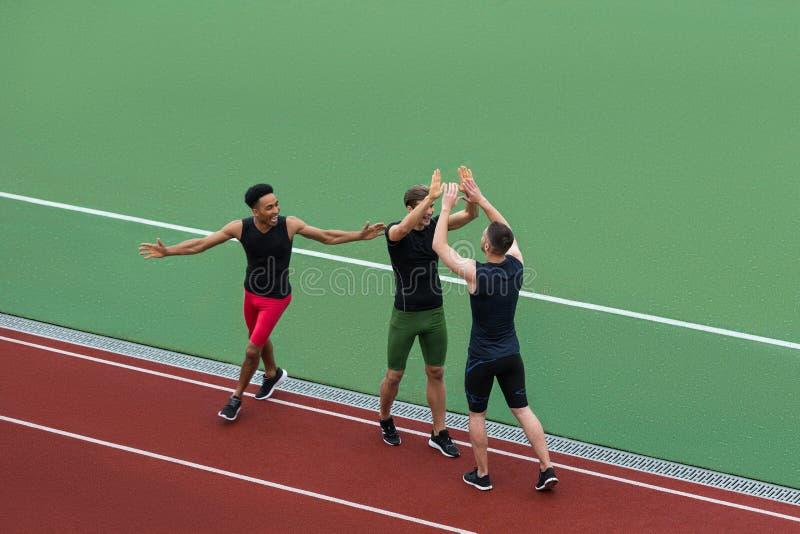 Equipo multiétnico del atleta que se coloca en pista corriente fotografía de archivo