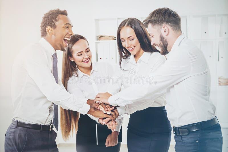 Equipo multicultural de colegas en una oficina con el togethe de las manos foto de archivo libre de regalías