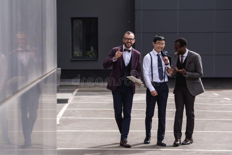 Equipo multicultural del negocio que camina en la calle cerca del edificio de oficinas moderno fotografía de archivo libre de regalías