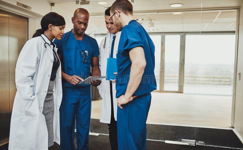 Equipo multirracial de doctores que discuten a un paciente imágenes de archivo libres de regalías