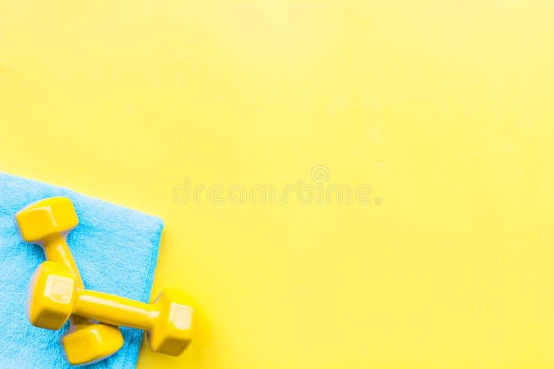 Equipo para el ejercicio del deporte Fondo de la aptitud Pesas de gimnasia en espacio amarillo en colores pastel de la copia de l imagen de archivo