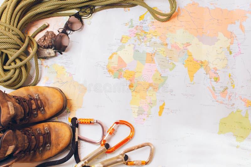 Equipo para subir a gran altitud: botas, cuerdas del deporte, carabinas en el fondo de un mapa geogr?fico imagenes de archivo