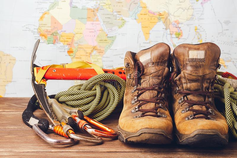 Equipo para subir a gran altitud: botas, cuerdas del deporte, carabinas en el fondo de un mapa geogr?fico Copie el espacio fotos de archivo