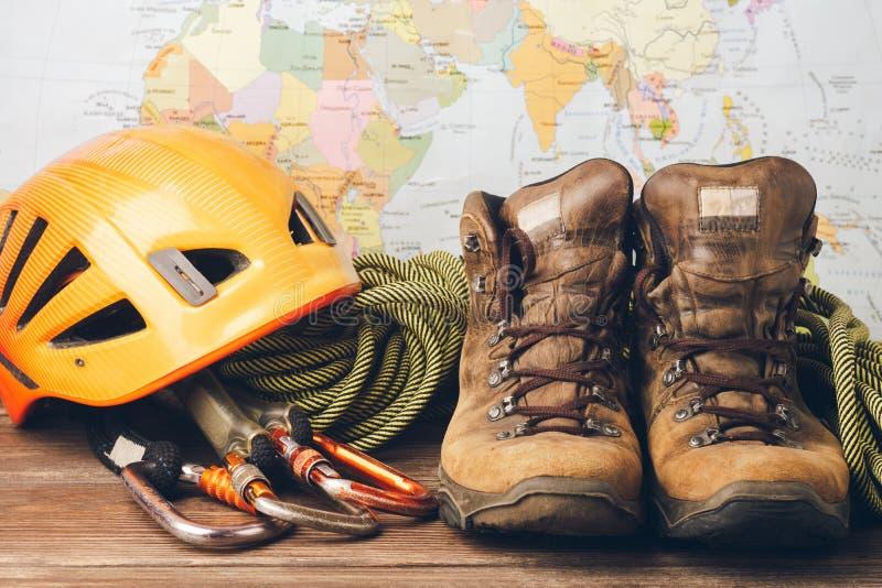 Equipo para subir a gran altitud: botas, deportes cuerda, carabinas en el fondo del mapa geográfico fotos de archivo libres de regalías