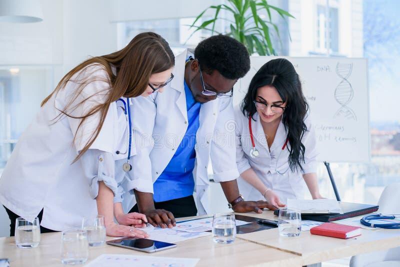 Equipo profesional de doctores que discuten resultados pacientes de las radiografías El grupo étnico multi de estudiantes de medi fotos de archivo
