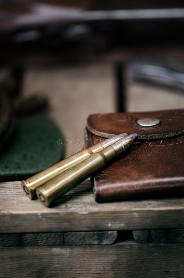 Equipo profesional de los cazadores para cazar Detalle en la munición Fondo negro de madera con el rifle, el sombrero, y otros eq fotografía de archivo libre de regalías