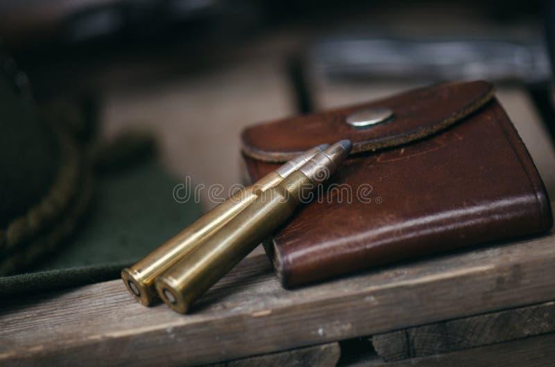 Equipo profesional de los cazadores para cazar Detalle en la munición Fondo negro de madera con el rifle, el sombrero, y otros eq fotos de archivo