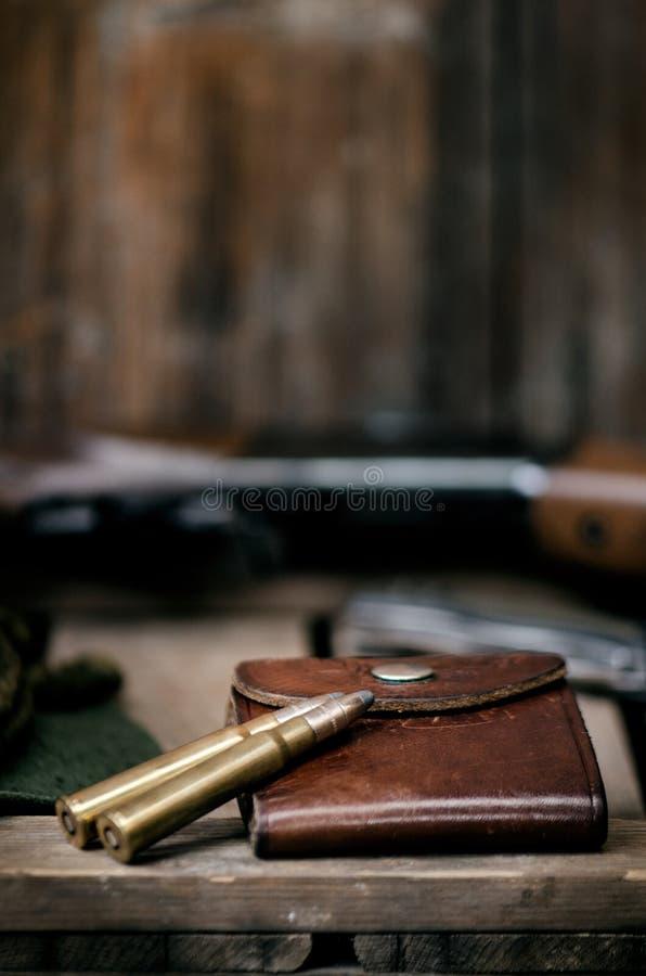 Equipo profesional de los cazadores para cazar Detalle en la munición Fondo negro de madera con el rifle, el sombrero, y otros eq imagenes de archivo