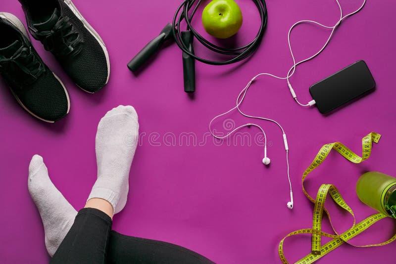 Equipo puesto plano del gimnasio tal como comba, botella de aguas, smartphone con el auricular, manzana y piernas humanas en calc imagenes de archivo