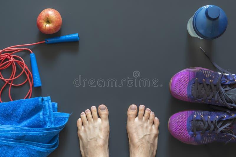 Equipo puesto plano del gimnasio tal como zapatillas de deporte y toalla de la comba con la manzana y las piernas humanas b imagen de archivo libre de regalías
