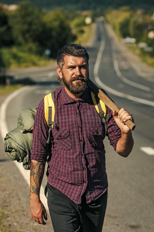 Equipo que acampa El caminante del hombre con la mochila turística y el hacha se colocan en el camino imagenes de archivo