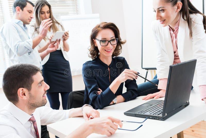 Equipo que da el informe de negocios al jefe en oficina fotos de archivo