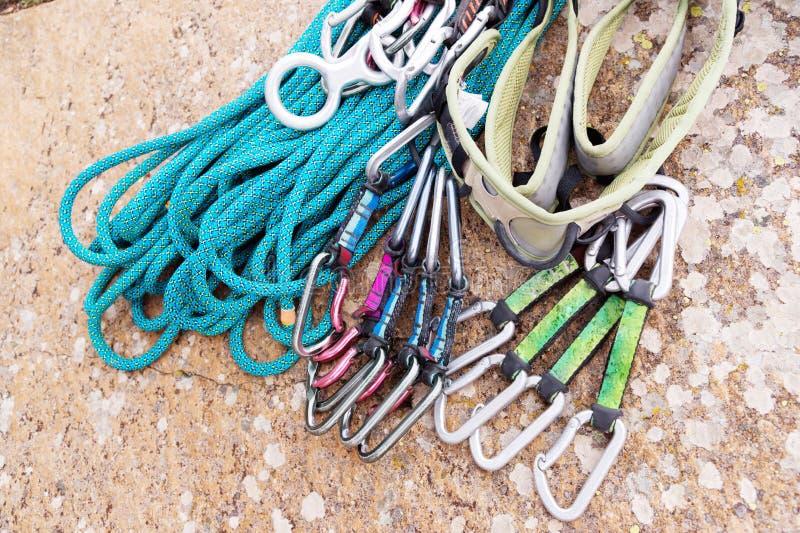 Equipo que sube - un arnés y una cuerda al lado de las carabinas mienten en una roca imagen de archivo libre de regalías
