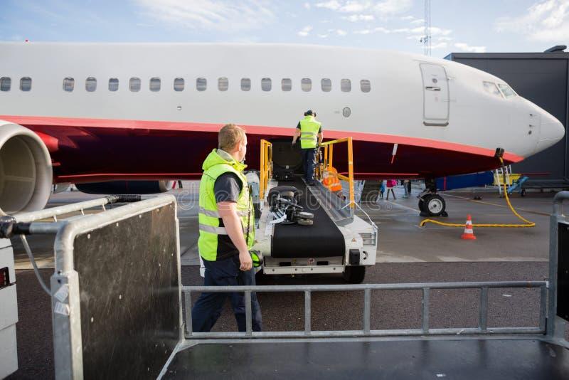 Equipo que trabaja en el transportador del equipaje atado al aeroplano imagen de archivo