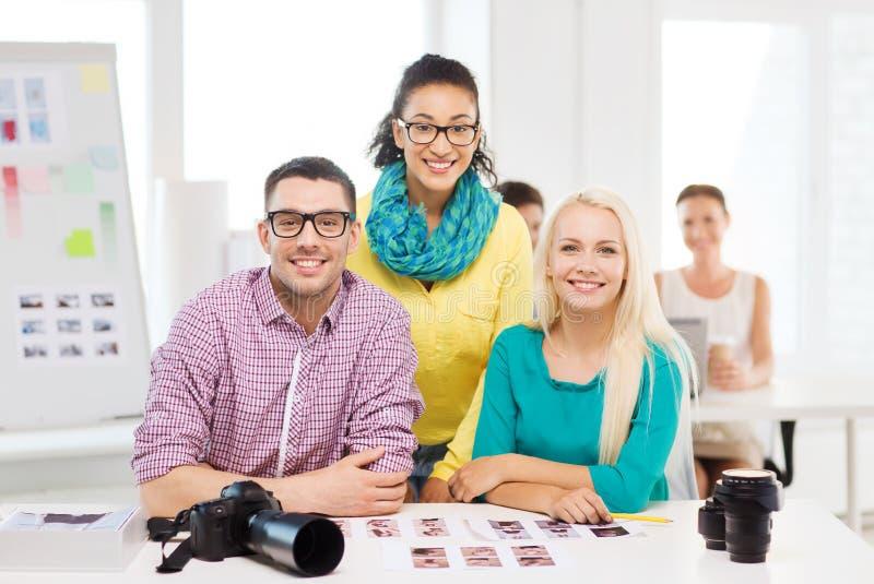 Equipo sonriente con las fotos impresas que trabajan en oficina imagen de archivo libre de regalías