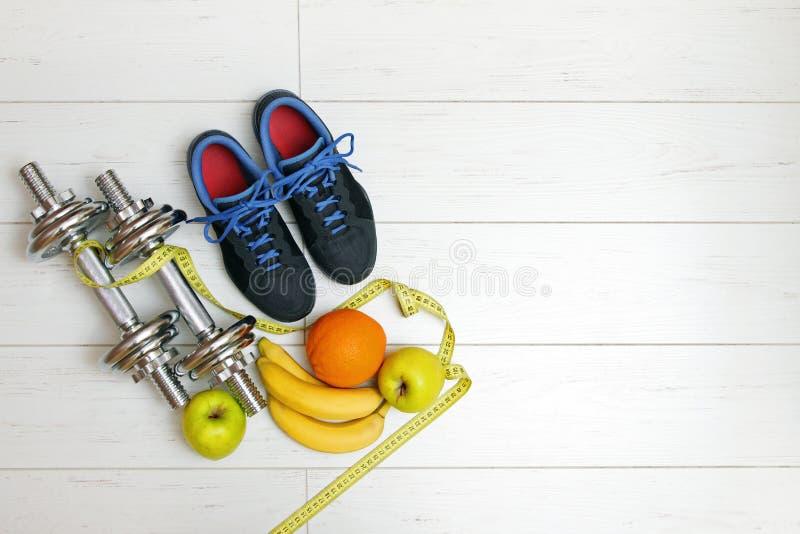 Equipo y frutas de la aptitud en el piso de madera blanco del tablón imágenes de archivo libres de regalías