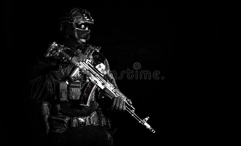 Equipped elite forces soldier low key portrait. Police assault team member, special forces soldier, private security service, military company serviceman in stock images