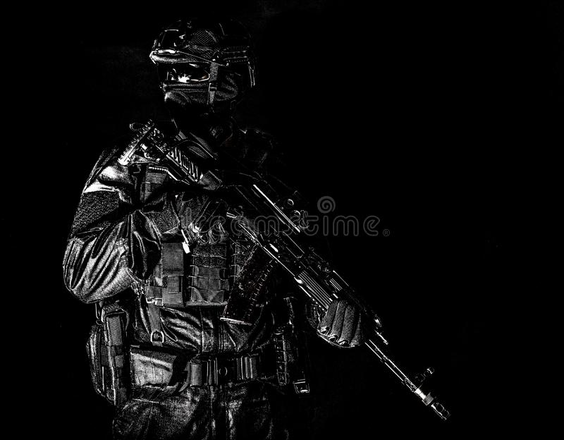 Equipped elite forces soldier low key portrait. Police assault team member, special forces soldier, private security service, military company serviceman in stock photography