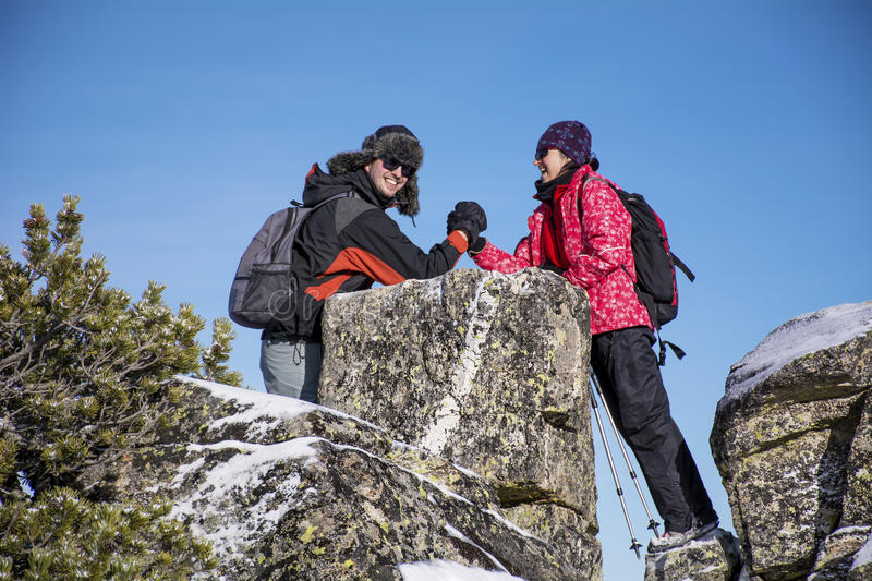 Equipped hiker woman and young man arm wrestling. Equipped hiker women and young men arm wrestling on a rocks in a winter mountain stock photo
