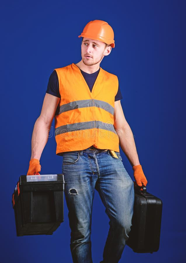 Equipped repairman concept. Worker, handyman, repairman, builder on calm face carries bags with professional tools. Man stock photography
