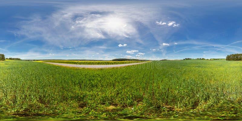 equirectangular球状等距离投射的充分的360度无缝的全景 一个领域的全景在一条路附近与 免版税库存照片