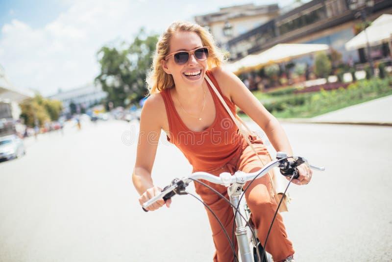 Equitação bonita da mulher na bicicleta imagem de stock