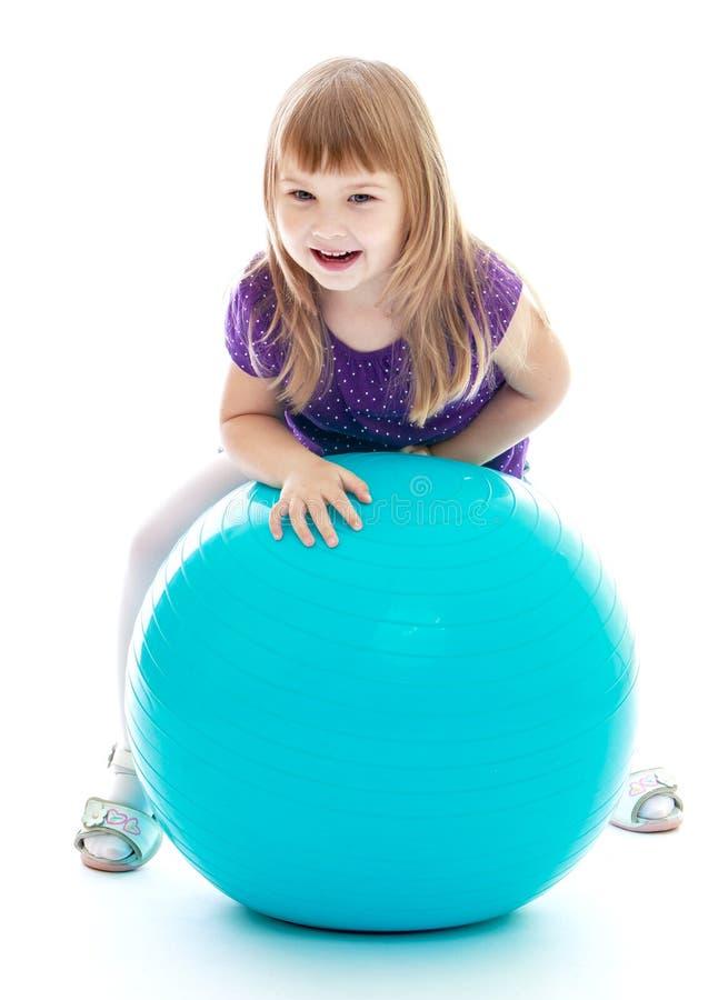 Equitação bonito da menina em uma bola grande foto de stock