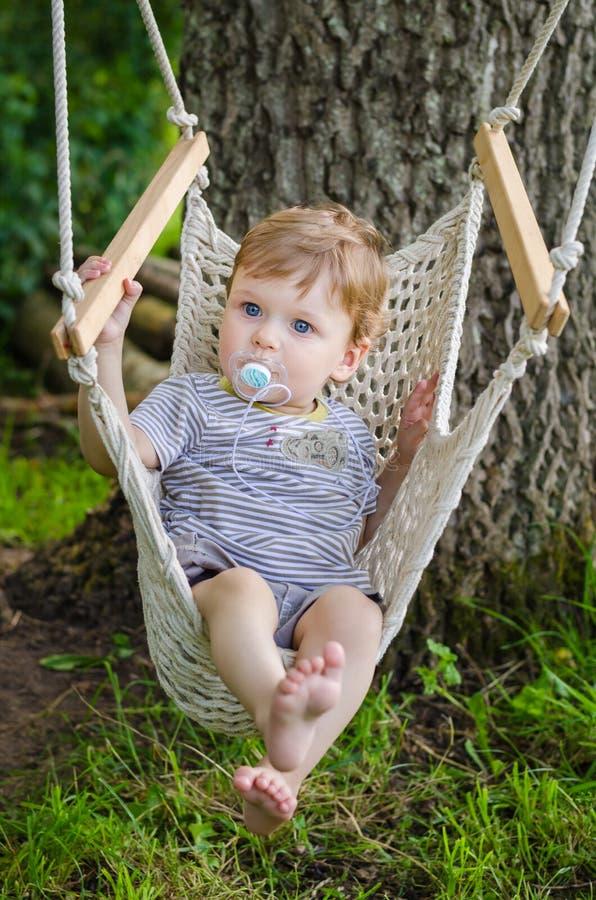 Equitação bonito pequena do bebê no balanço da rede no parque foto de stock royalty free