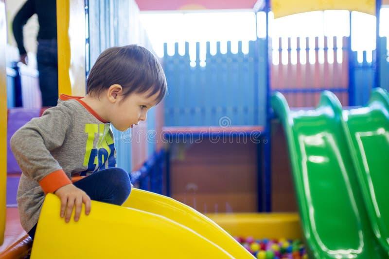 Equitação da criança das corrediças das crianças no centro de jogo A criança feliz, crianças que montam acima, para baixo na corr fotos de stock