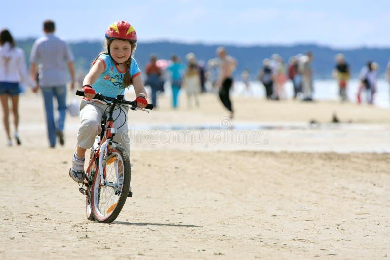 Equitação da menina com a bicicleta ao longo da praia fotos de stock