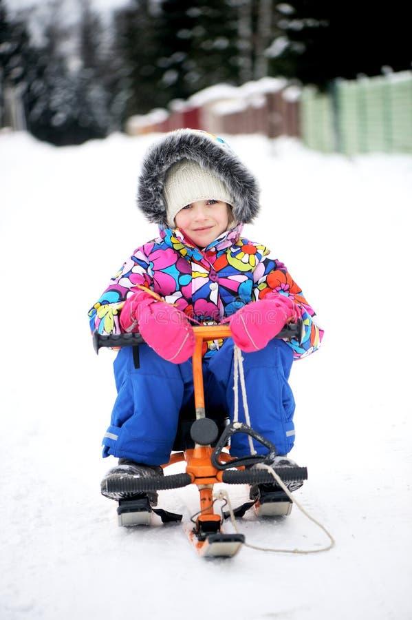 Equitação da menina da criança seu 'trotinette' da neve imagem de stock