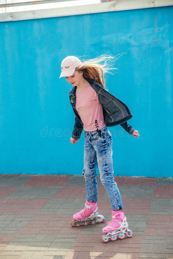 Equitação da menina do adolescente em patins de rolo no parque exterior do patim foto de stock