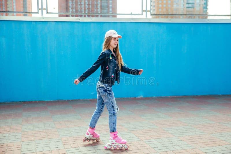 Equitação da menina do adolescente em patins de rolo no parque exterior do patim fotografia de stock
