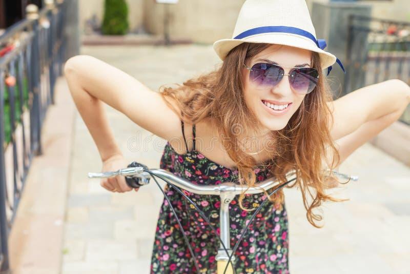 Equitação da mulher do close up pela bicicleta da cidade do vintage no centro da cidade imagem de stock