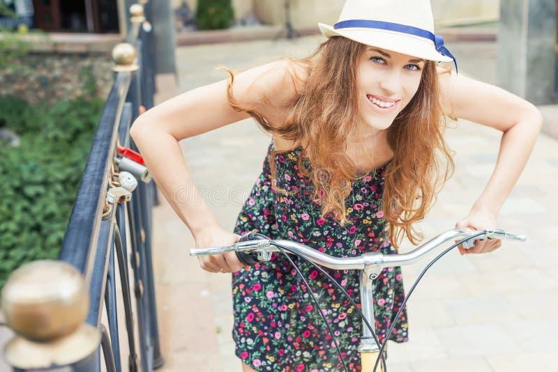 Equitação da mulher do close up pela bicicleta da cidade do vintage no centro da cidade foto de stock royalty free