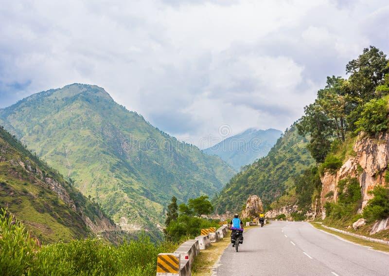 Equitação de dois ciclistas na estrada da olá!-montanha imagem de stock royalty free