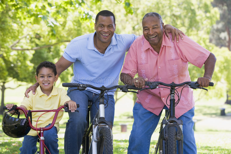 Equitação de primeira geração da bicicleta do neto e do filho fotografia de stock