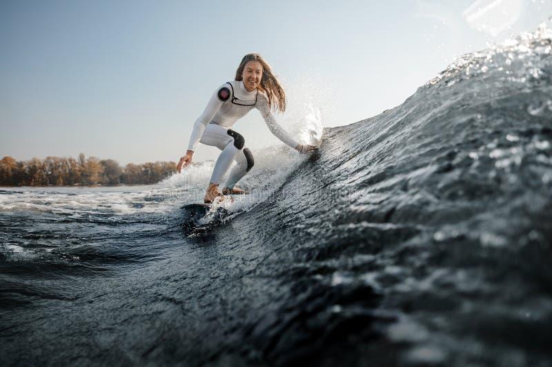 Equitação de sorriso da menina no wakeboard nos joelhos de dobra imagens de stock royalty free