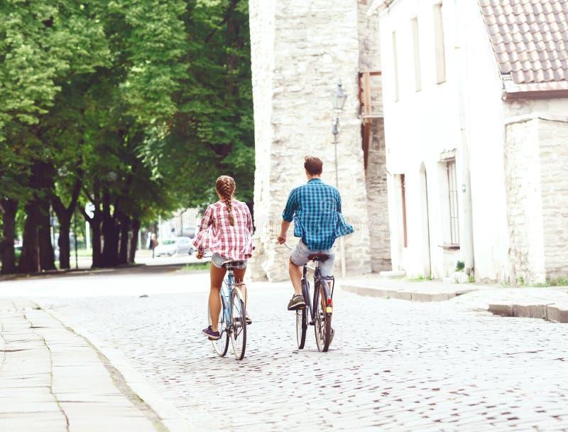 Equitação de viagem feliz dos pares em bicicletas Noivo e girlfri imagens de stock royalty free