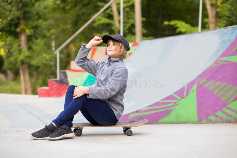 Equitação desportiva nova da menina no longboard no parque imagens de stock