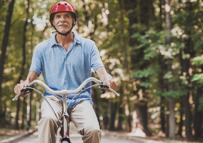 Equitação do ancião na bicicleta no parque no verão fotos de stock royalty free