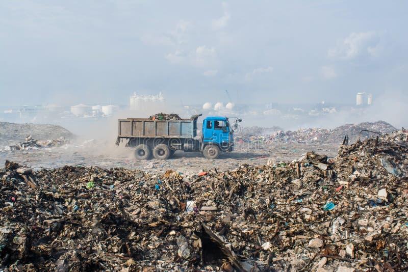Equitação do caminhão na descarga de lixo completamente do fumo, da maca, de garrafas plásticas, de desperdícios e de lixo na ilh foto de stock royalty free