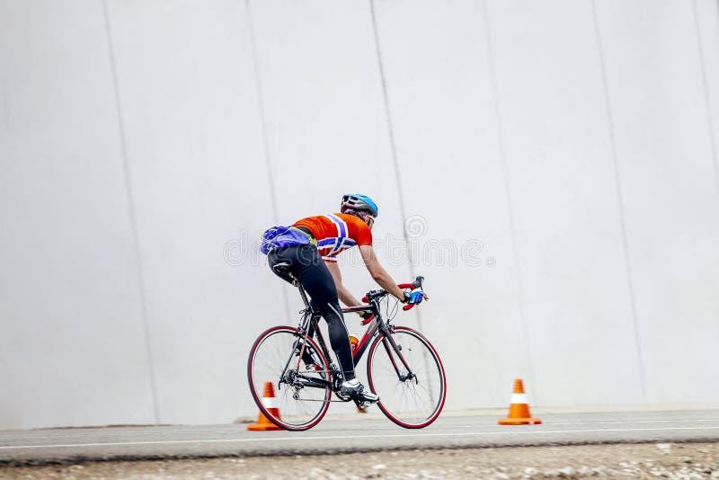 Equitação do ciclismo de multi-dia do ciclista do atleta na estrada com o cone alaranjado do tráfego foto de stock royalty free