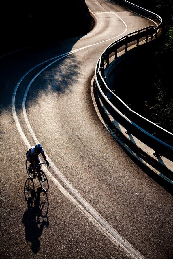 Equitação do ciclista ao longo de uma estrada da montanha imagem de stock royalty free