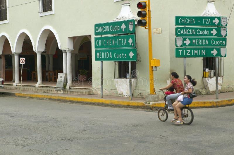 Equitação do ciclista através do centro de cidade da vila colonial de Valladolid, na península do Iucatão, México com os sinais q fotos de stock