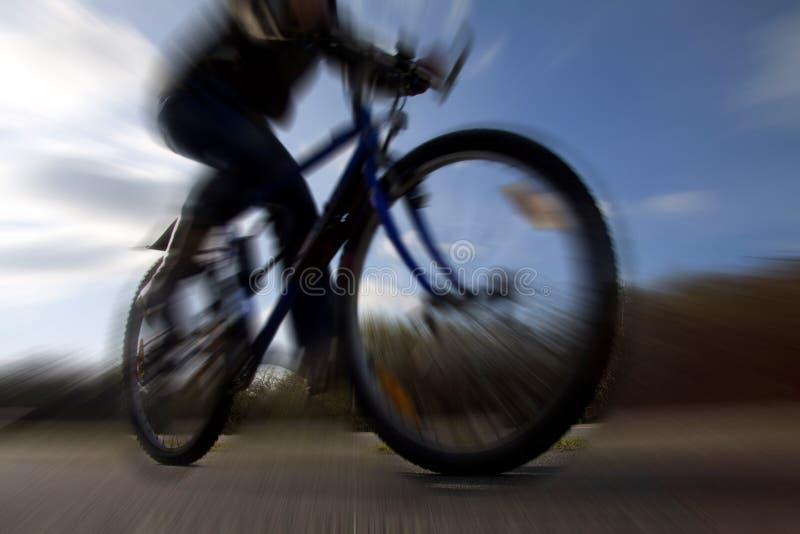 Equitação do ciclista no Mountain bike na perspectiva e deliberadamente no movimento dramáticos da silhueta borrado foto de stock