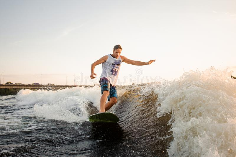 A equitação do homem atlético e novo no wakesurf abaixo do rio acena fotos de stock