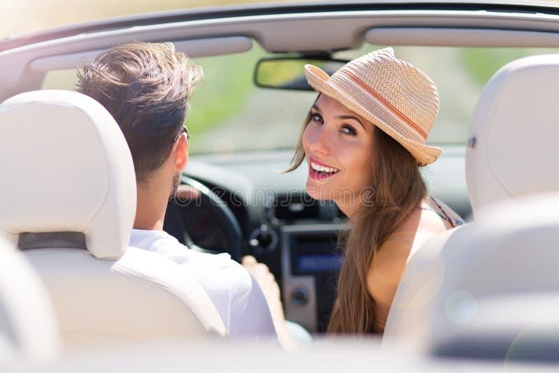 Equitação do homem novo e da mulher no carro convertível imagens de stock